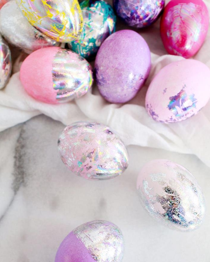 lots of easter eggs, dyed in pale and dark pink, purple and teal, silver and yellow, easter egg designs, decorated with glittering hologram paint