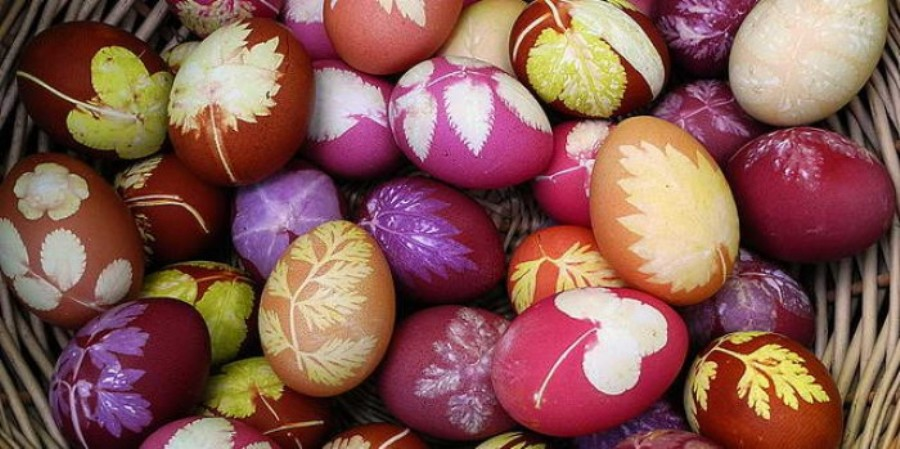 a variety of eggs, dyed in pink and red, orange and yellow, with different botanical shapes printed on them, in white yellow and green, easter egg coloring with with flowers