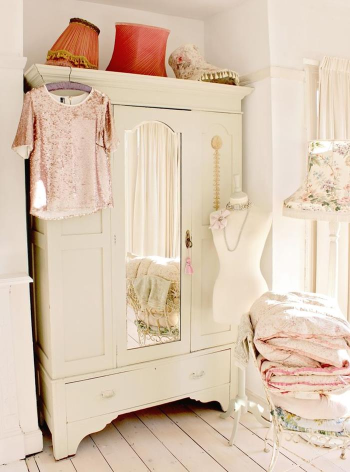 wardrobe in vintage style, painted white and featuring a mirror, inside a room with cream floors, shabby chic decorating, clothes and duvets on a vintage chair