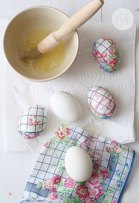 floral paper napkin in blue, pink and green, near two plain white eggs, and three eggs decorated with decoupage, coloring easter eggs, beige bowl with egg whites nearby