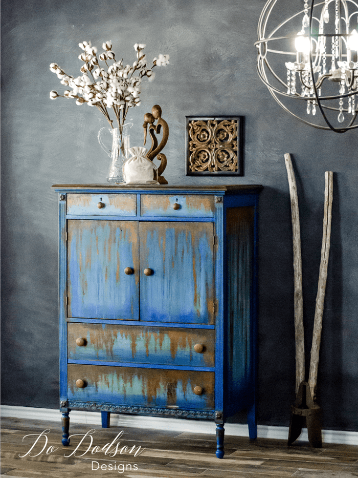 bright blue vintage cabinet, with orange paint effect resembling rust, near dark grey unevenly painted wall, and various decorations