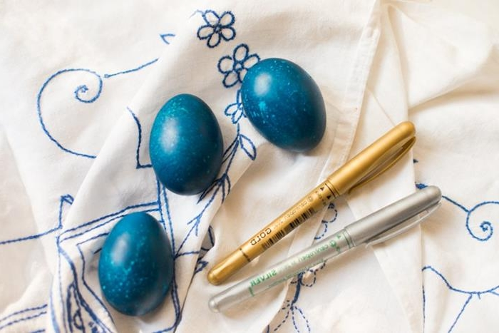 spotty blue eggs, placed on cream fabric, with blue floral embroidery, how to dye easter eggs, near a gold and a silver pen