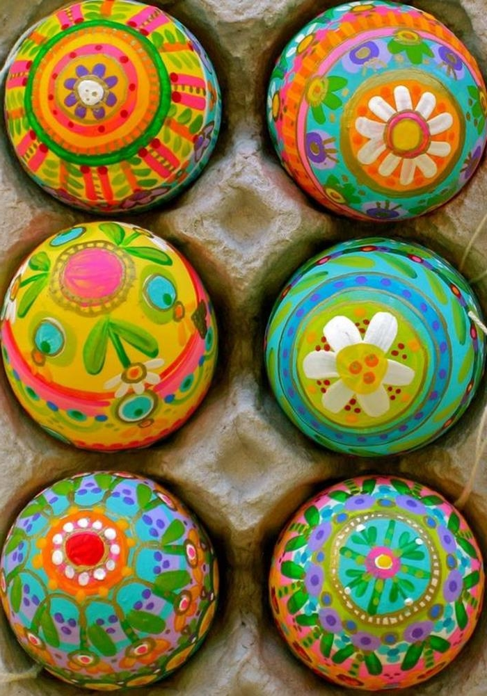 multicolored eggs painted by hand, with patterns featuring flowers and circles, easter egg ideas, placed inside a cardboard egg box