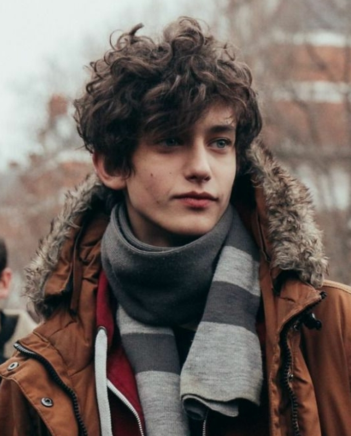 smiling teen with brunette, curly and messy hair, hair designs for boys, rebellious look, combined with brown, hooded winter jacket, and grey striped scarf