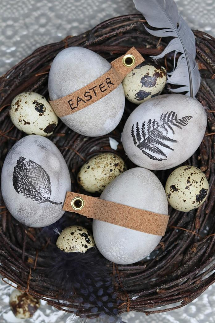 quail eggs placed inside a nest, made from brown twigs, near feathers and four hen's eggs, dyed in pale spotty grey, and decorated with leaf patterns and labels