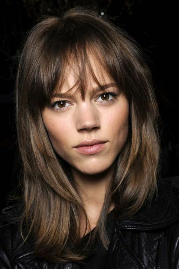discreet make up, worn by brown-eyed young woman, messy layered hair and fringe, medium length brown hair, black leather jacket