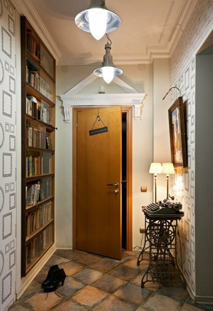 ajar wooden door, leading into a hall, with floors covered in rough stone tiles, patterned wallpaper and wooden bookshelves, antique typewriter on table, near two lamps and a framed painting, hallway decor ideas
