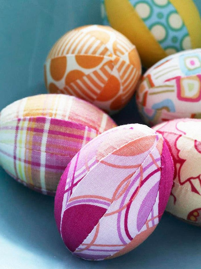fabric pieces with patterns in different colors, sewn together, covering six eggs, easter egg designs