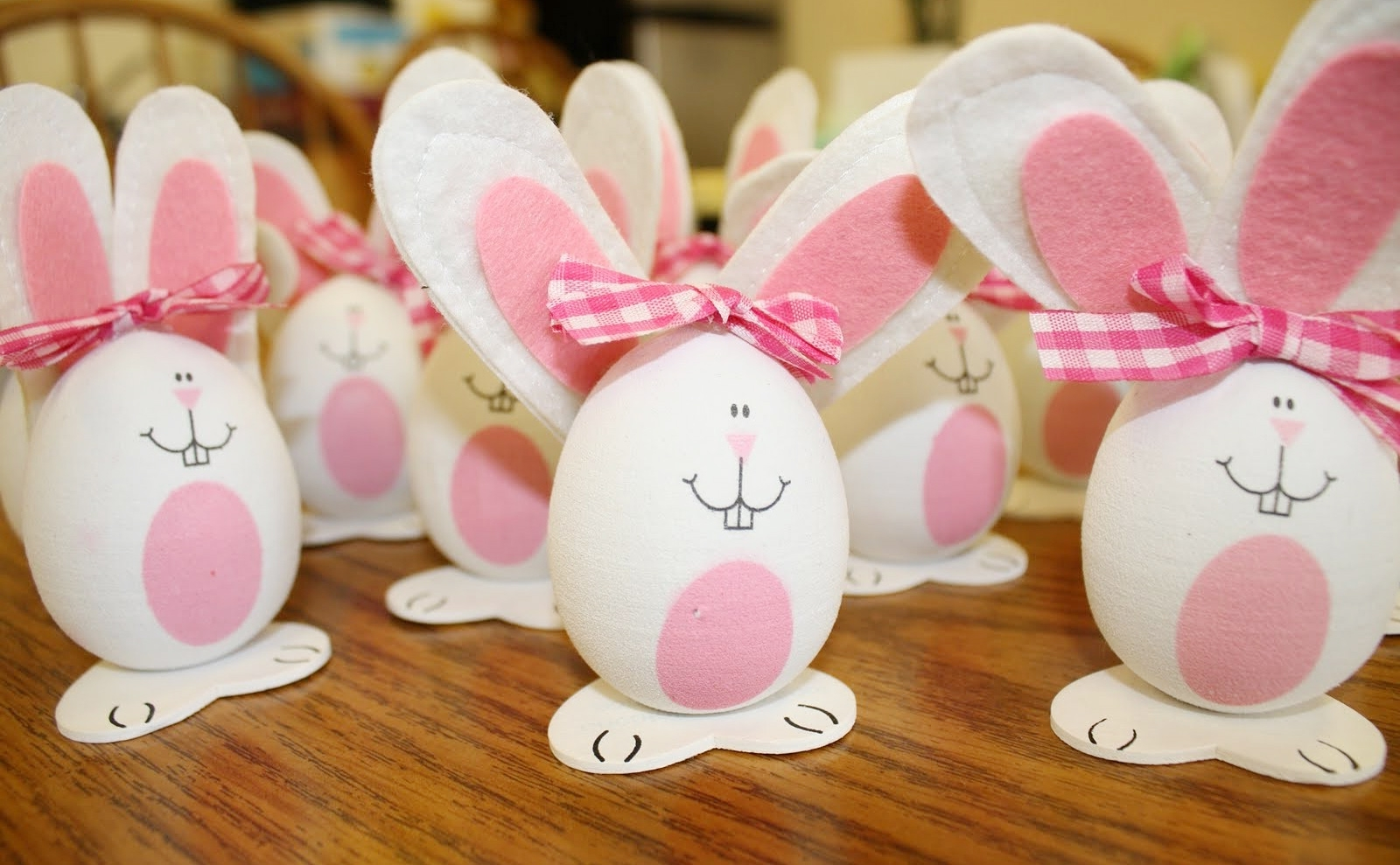 rabbits made from white eggs, easter egg designs, decorated with white and pink felt ears, fabric bows, and hand-drawn faces