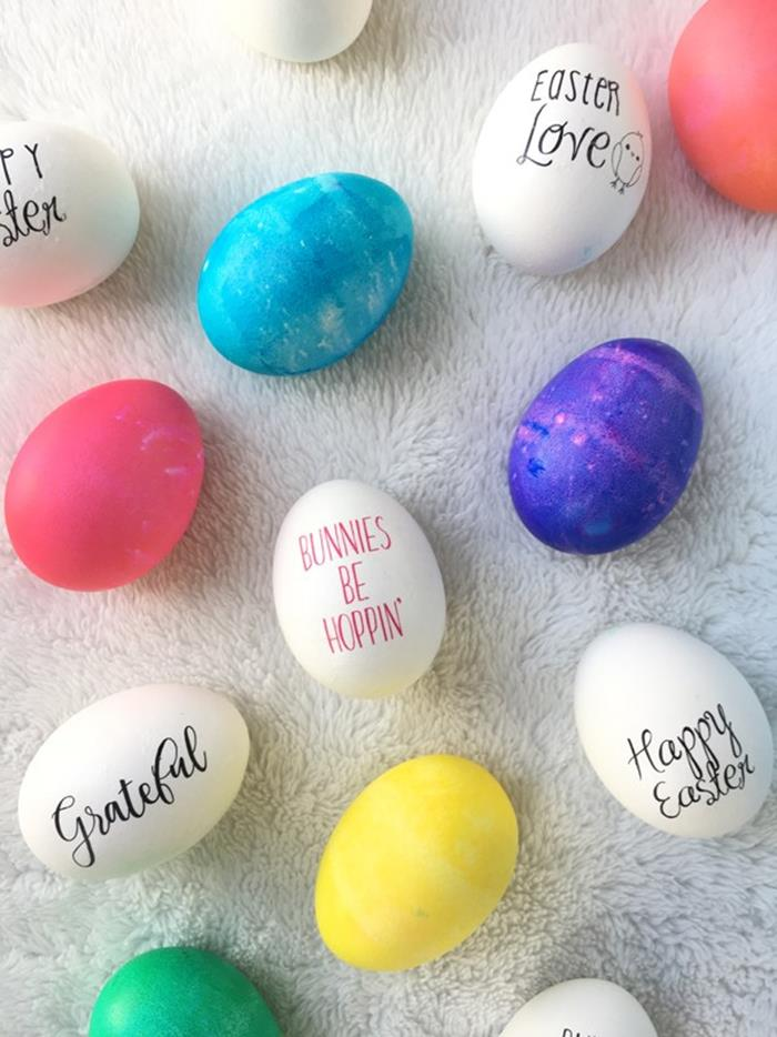messages written in different fonts, in red and black, on white eggs, placed on white surface, near pink and blue, yellow green and purple dyed eggs, easter egg coloring variations