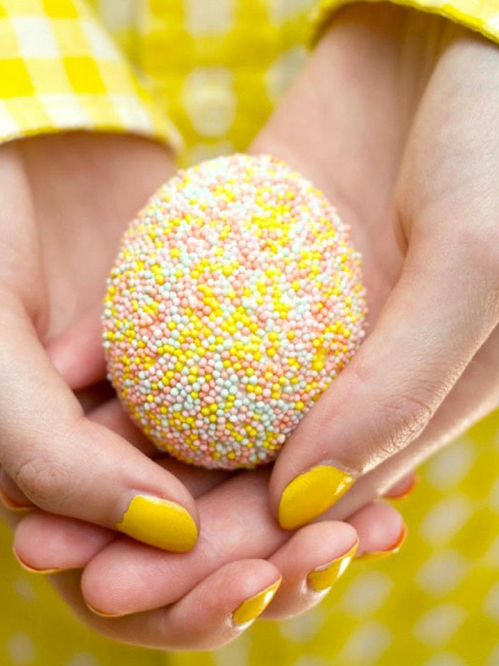 sprinkle-covered ester egg, in yellow and white, pale blue and pink, held by two hands with yellow nail polish, and white and yellow chequered sleeves