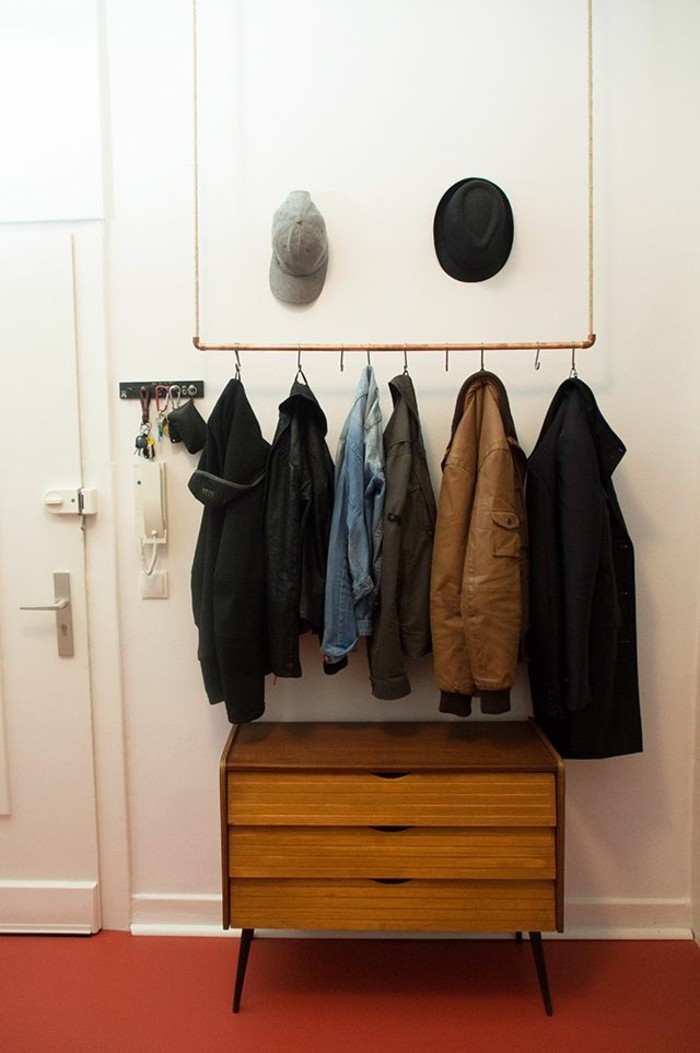 minimalist clothes hanger, hanging from ceiling, with several coats hung on it, brown retro cupboard underneath, red floor and white walls, hallway design ideas, two hats hung on wall