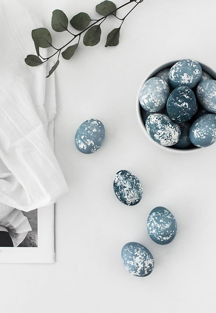 spotted dark blue dyed eggs, placed on white surface, near branch with green leaves, and a framed portrait, almost covered in white cloth