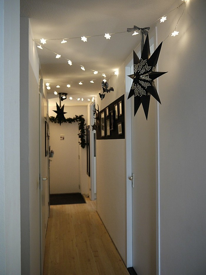 simple narrow corridor, with white walls and doors, decorated with lit star-shaped chain lights, black garlands, and large black star lanterns