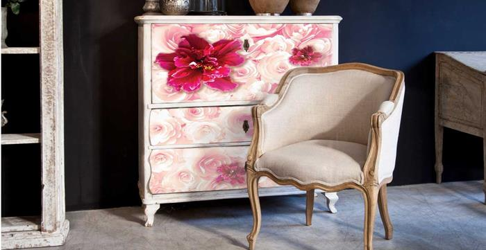 fuchsia and pale pink flowers, painted on white antique chest of drawers, near a pale beige armchair, with wooden legs and armrests