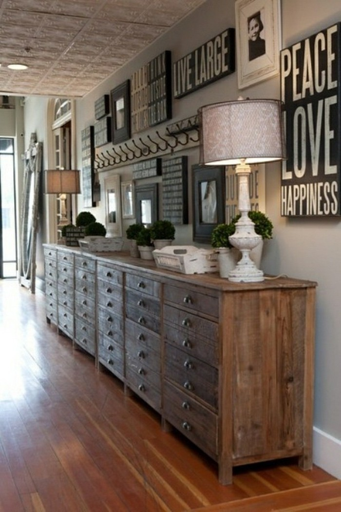 massive solid wood chest of drawers, decorated with lamps, potted plants and other items, on wooden floor, next wo pale grey wall, covered with framed images, and inspirational messages