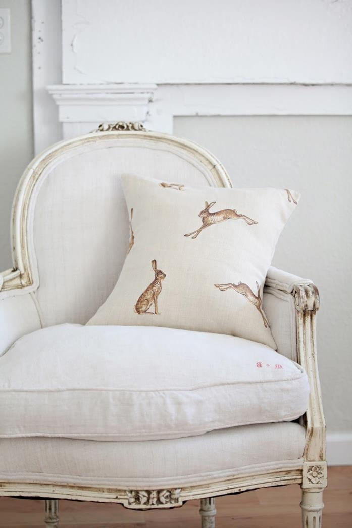 hare print pale cream cushion, on off-white antique chair, with ivory-colored details, country cottage furniture, white background and wooden floor
