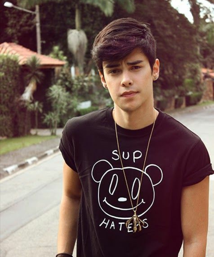 hair designs for boys, dark-haired youth, with voluminous asymmetrical fringe, and deep side part, wearing black t-shirt with white graphic, crow-foot silver necklace, and stud earrings