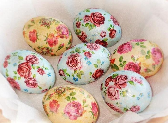 rose patterned easter eggs, in pale blue and pale yellow, made with decoupage techniques, placed on a white napkin