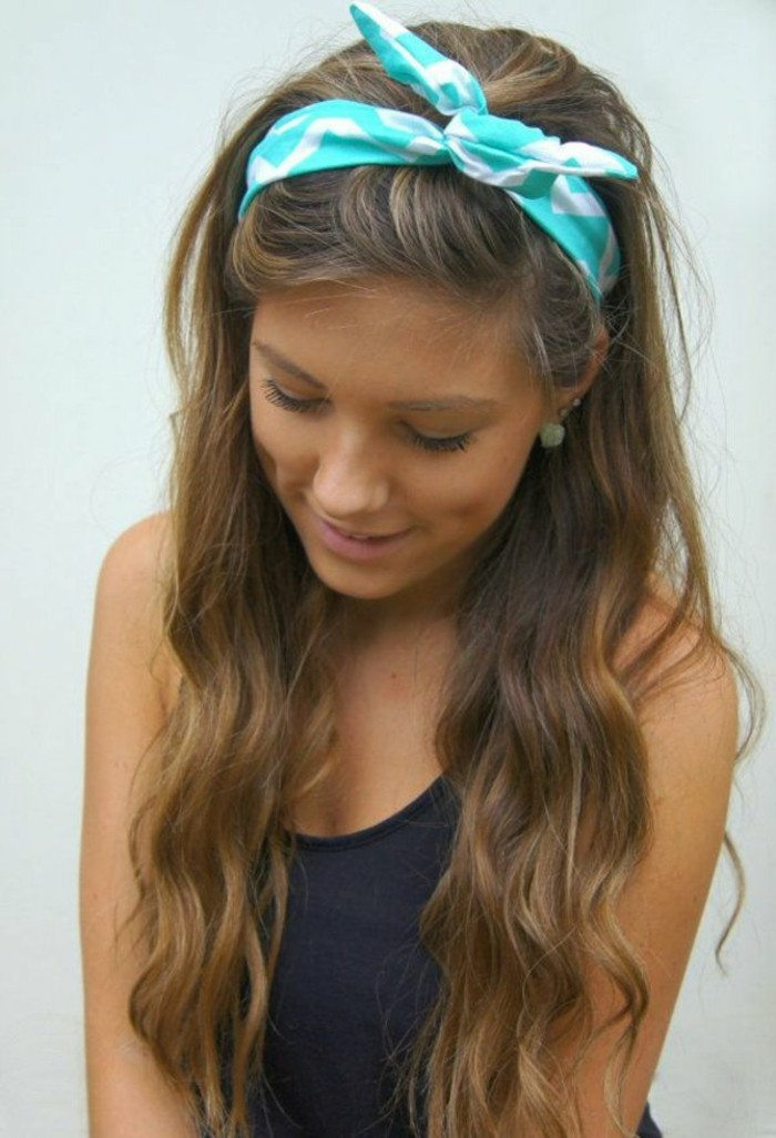 dimpled girl with discreet make up, and long wavy brown hair, with dark blonde highlights, wearing black tanktop, and teal and white headband