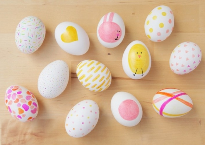 twelve white eggs, decorated with drawings of a chick and bunny, hearts and dots, lines and spots, all in pink orange and yellow, easter egg ideas