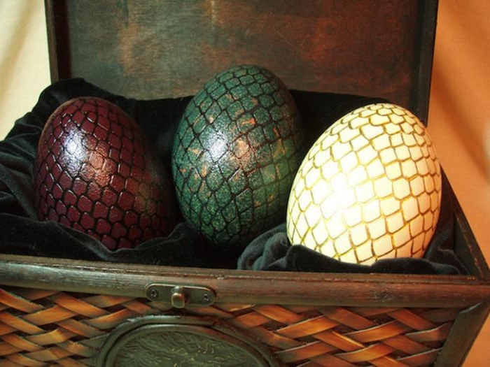game of thrones inspired dragon easter eggs, ostrich eggs painted in yellow, green and dark red, with hand-drawn golden and black scales, placed inside a chest