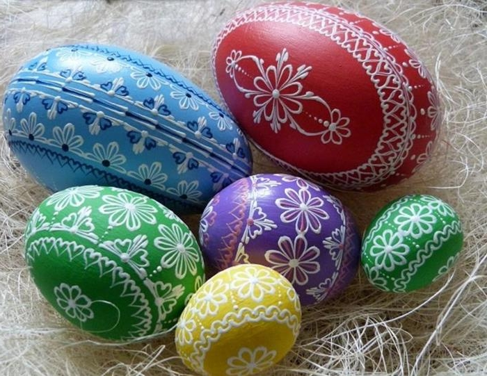 traditional eastern european easter eggs, different sizes dyed in red, blue and green, yellow and purple, and decorated with complex, white floral patterns
