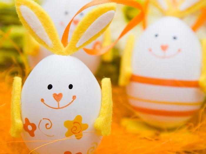 bunny made from white egg, decorated with a hand-drawn face, yellow felt ears and arms, and small flower stickers, easter egg designs, more similar eggs in the background