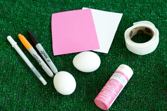 sheets of paper in white and pink, placed on artificial grass, near roll of white masking tape, a tub of pink paint, two white eggs, and three markers, coloring easter eggs