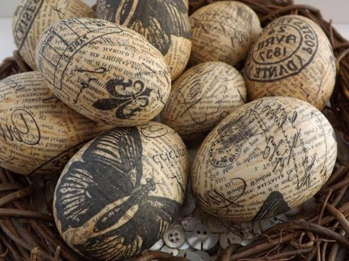vintage newspaper decoupage easter eggs, decorated with black stamp-like patterns, butterflies and fancy writing, placed in a nest with many clothes buttons