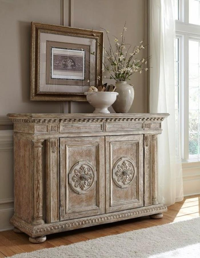 distressed and worn beige paint effect, on large antique wooden cupboard, framed painting and vases