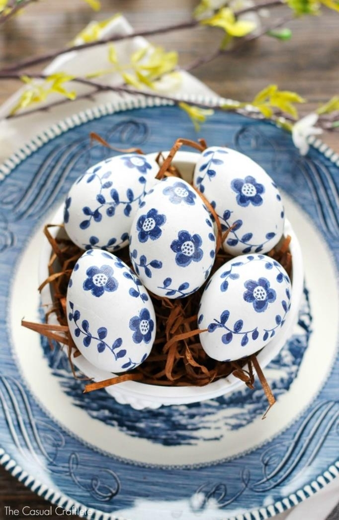 inky blue flower patterns, hand-drawn on white easter eggs, placed in a white bowl, filled with brown easter grass