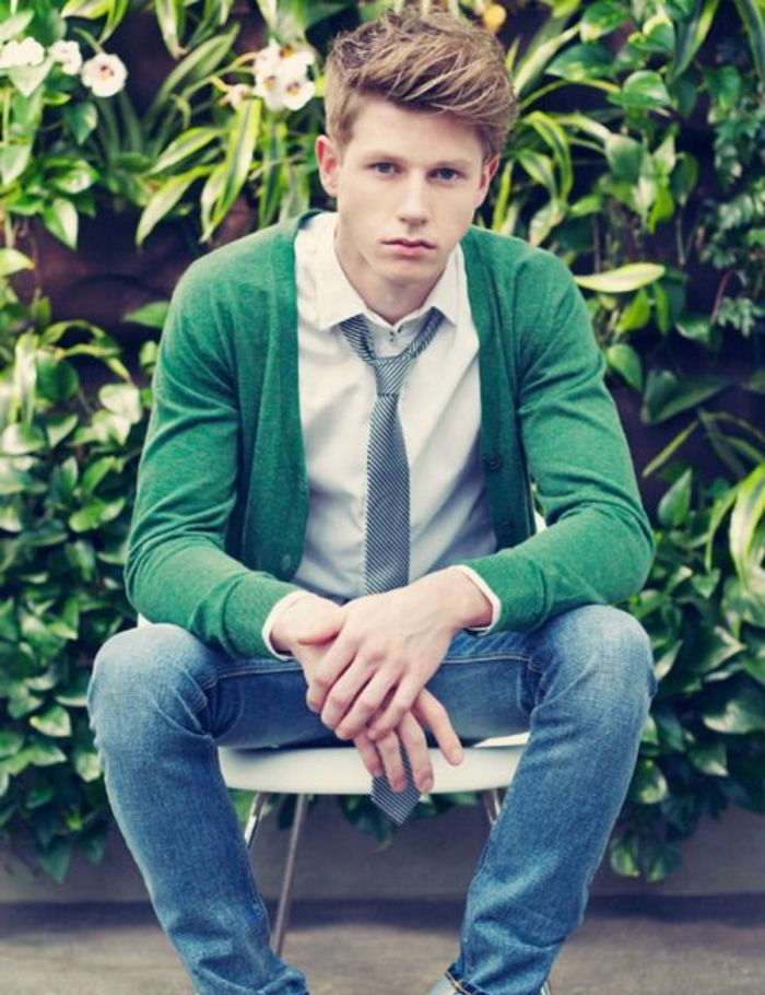 sitting teenager in jeans and white shirt, with grey necktie and green cardigan, dark blonde hair, styled in a messy quiff, short at the sides like in boys fade haircut