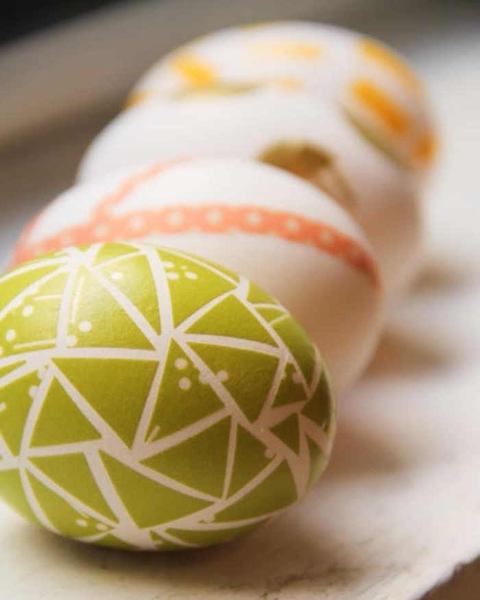 washi tape used as easter egg decoration, on four white eggs, green triangular shapes, orange stripes, brown and yellow shapes