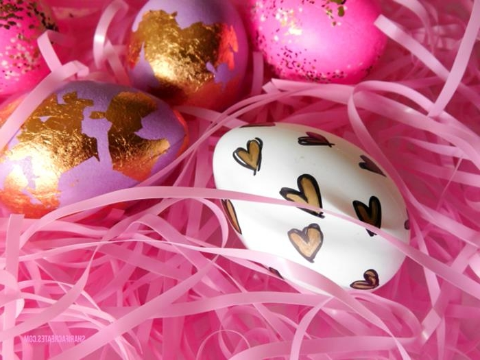 plastic easter grass in pink, two pink eggs, partially covered in gold leaf, one white egg, decorated with hand-drawn hearts, in black and gold