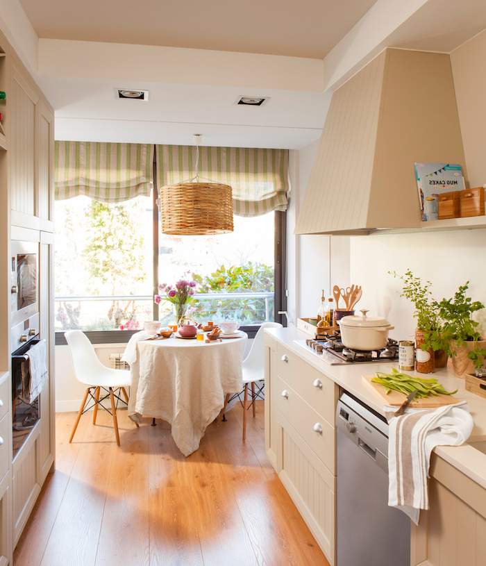 bright kitchen with diningroom space, wooden floors and white walls, cream-colored furniture and appliances, shabby sheek curtains and potted plants