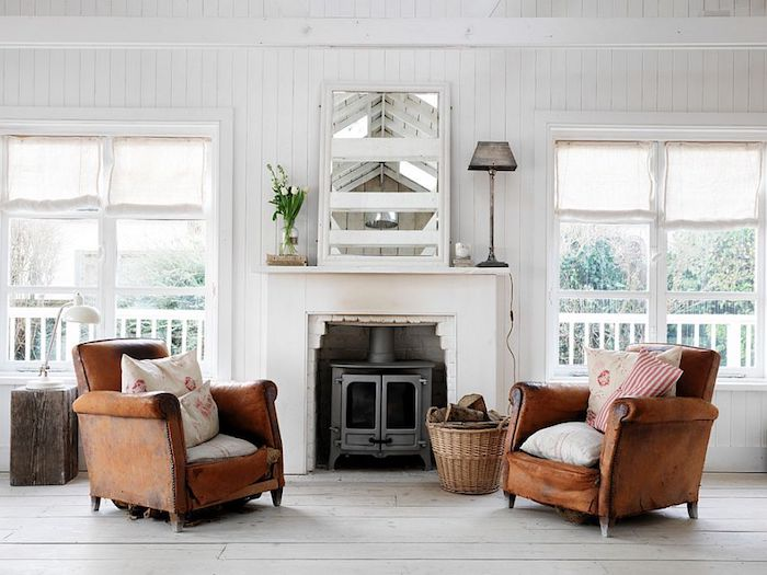 worn leather armchairs, in warm brown, with shabby-chic cushions, off-white wooden floor, fireplace and mirror