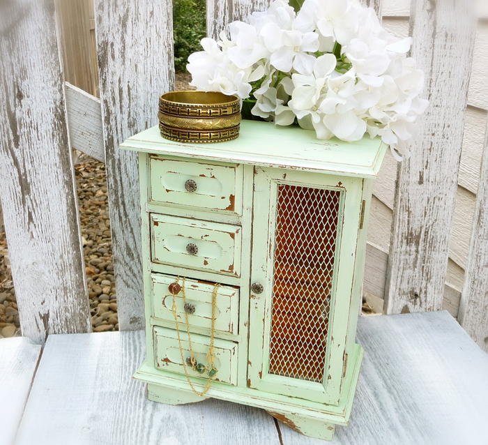 small wooden cabinet in pale green, with four tiny drawers and a compartment, shabby chic furniture, large gold bangle, and white flowers placed on top of it