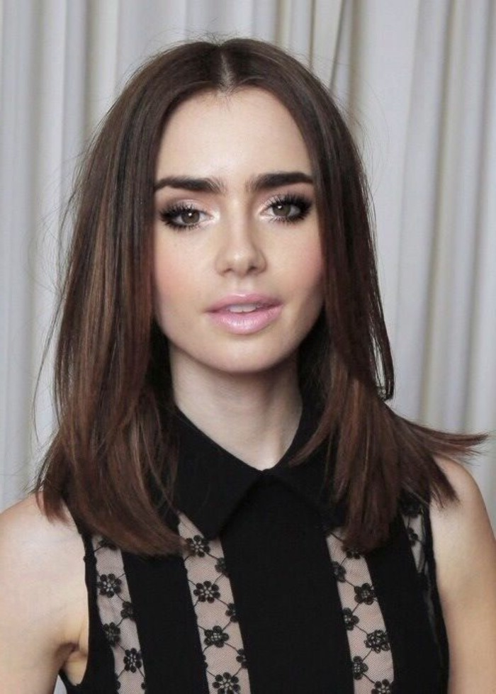 dark haired actresses, lily collins wearing a sleeveless black shirt, with floral lace inserts, brown layered hair, parted in the middle, pale pink lipstick, black mascara and pale purple eye make up