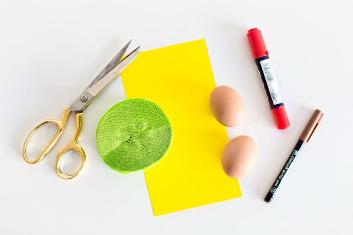 brown and red markers, dying easter eggs, a sheet of yellow paper, a roll of light green paper, a pair of scissors, two brown eggs,