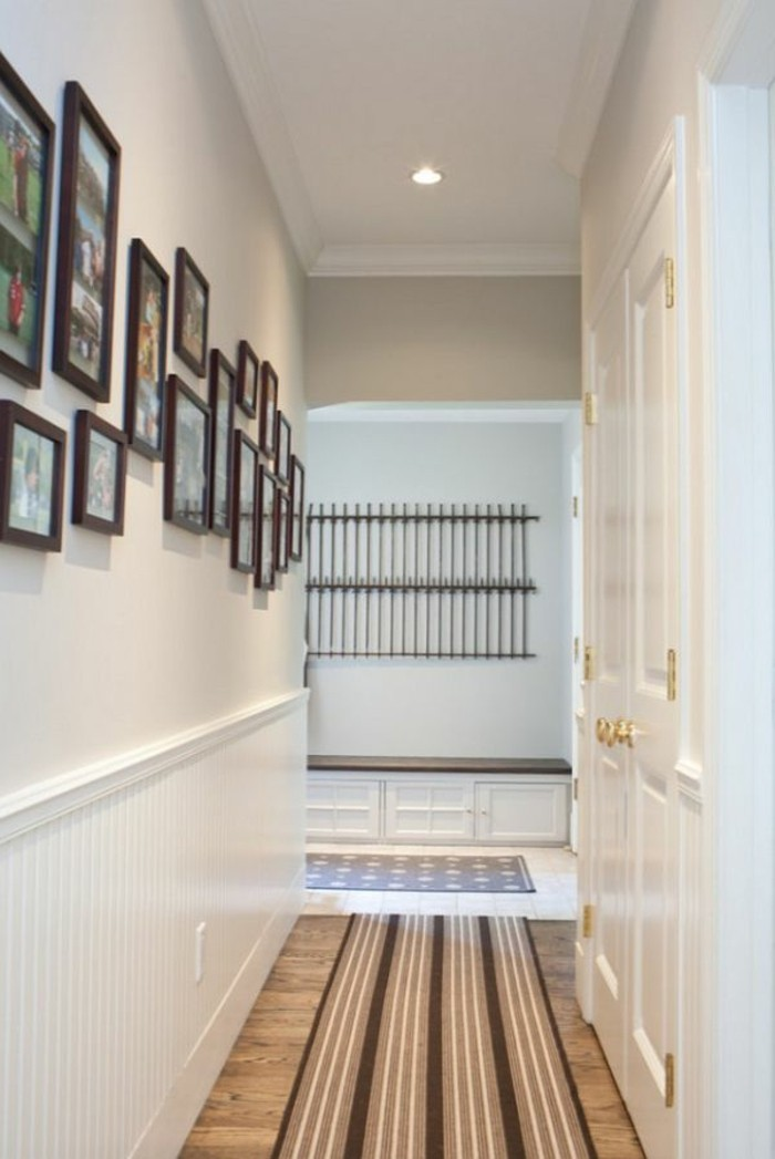 brown frames in different sizes and shapes, containing family photographs, mounted on white wall, small hallway ideas, in corridor with white doors, wooden floor and a striped rug