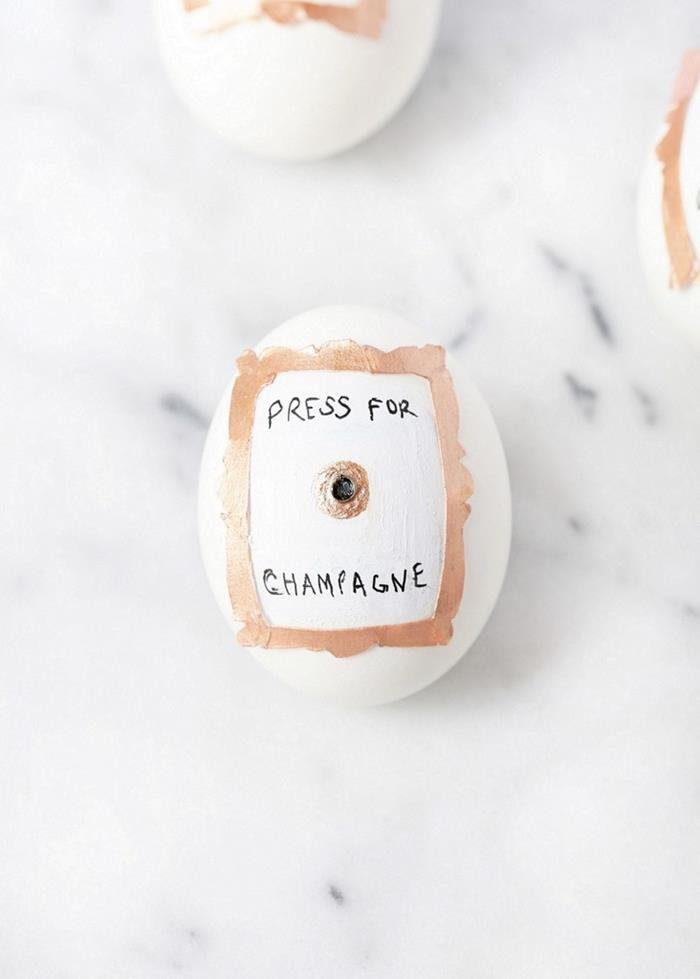 press of champagne, written in plack sharpie, near a drawing of a button, and a small frame, stuck on a white egg, easter egg decorating