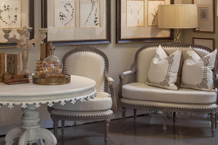 round ornamental coffee table in white, near cream and beige colored chair, and matching shabby chic sofa, with two cushions, shabby sheek decorations