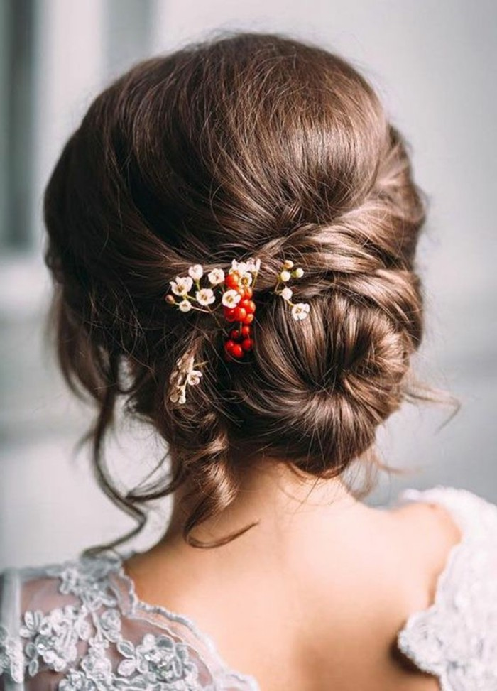 special occasion bun, with twists and curls, decorated with small red berries, and tiny white flowers, brunette hair colors, on woman wearing white lace top, with open back