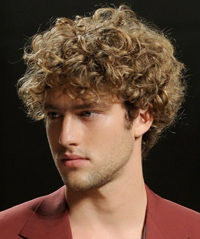 messy dark blonde mop top, naturally curly hair, long hairstyles for boys, on young man with stubble, wearing a red blazer