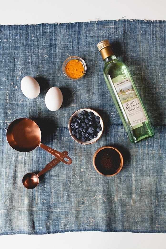 worn blue fabric, with two white eggs, a bottle of vinegar, a bowl of blueberries, a small bowl of ground coffee, a tiny glass bowl of ground turmeric, a small pan and a measuring spoon, easter egg ideas