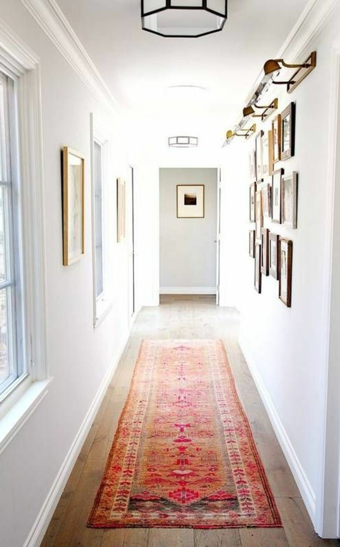 oriental multicolored rug, on wooden floor, inside white corridor, hallway design ideas, with windows and many framed images