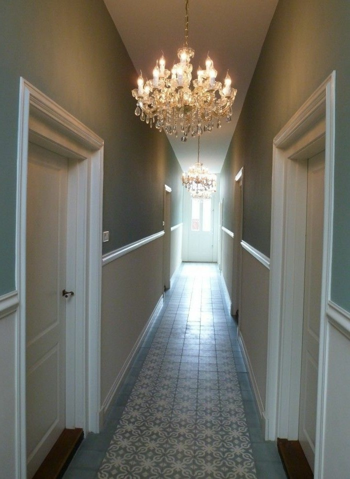 duck's egg blue walls, inside a corridor with white paneling, and four white doors, hallway design ideas, two lit crystal chandeliers, patterned pale blue tiles on floor