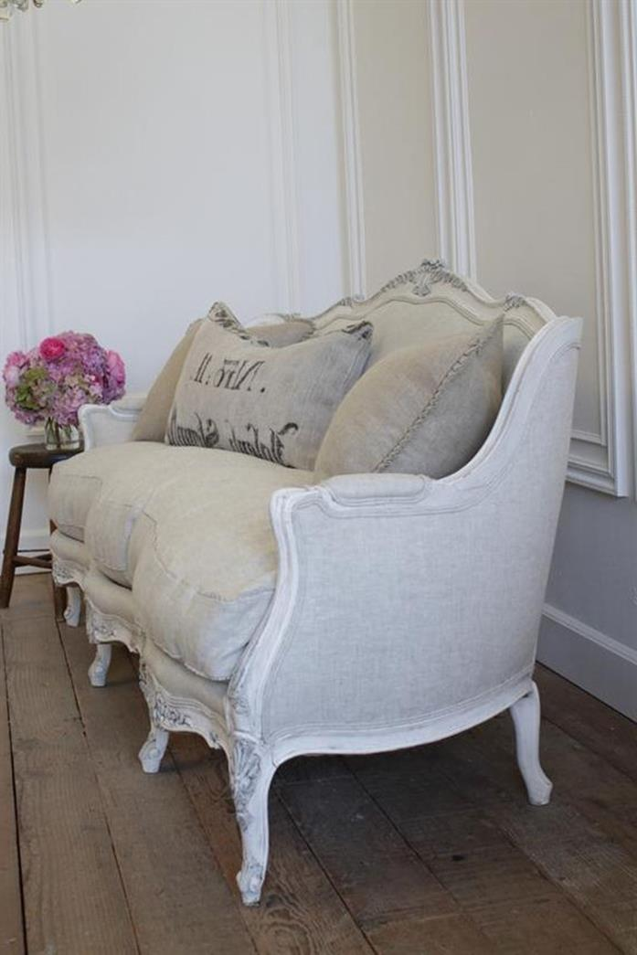 pale grey and white french sofa, with matching cushions, and white armrests and legs, on rough vintage wooden floor, near stool with flower vase