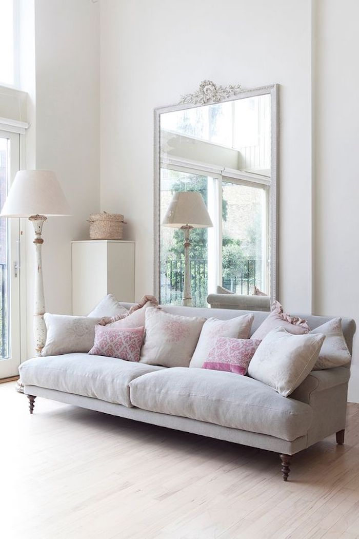 cushions in pale grey and pink, plain and patterned, placed on soft, pale grey modern french sofa, large mirror in white frame, and lamp nearby